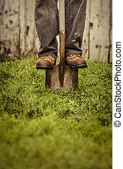 Details of feet and Shovel in front of Barn