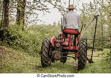 Young Farmer on a Vintage Tractor - Young Farmer Driving a...