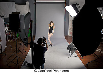 The photographer photographs the professional model -...
