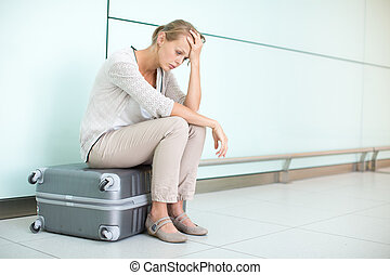 Young, female frustrated passenger at the airport, waiting...
