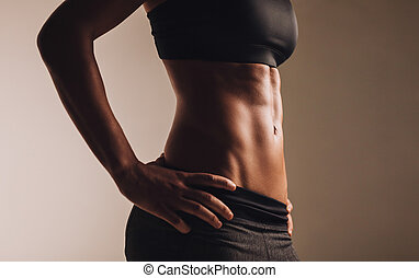 Cropped image of woman's waist. Perfect abdominal muscles of...