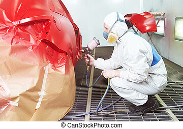car painting in chamber - auto repair worker painting a red...
