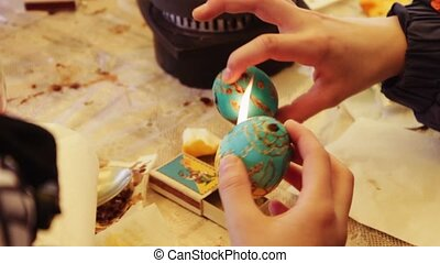 Man paints the Easter Egg