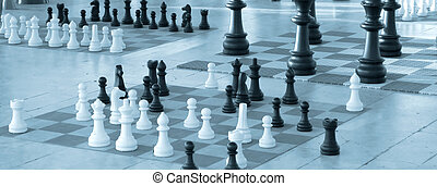 Chess pieces in diferent size on a chess boards - Blue tint