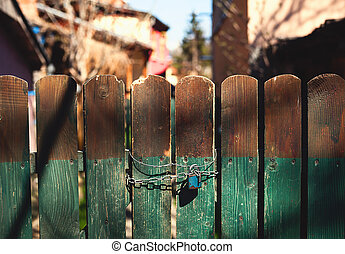 Old Wooden Gate - Old wooden gate locked with a chain and...