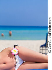 Womans body is lying on the beach close-up