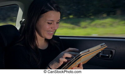 woman chatting with tablet in car - Woman surfing web...