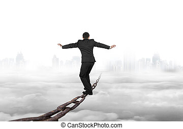 Businessman balancing on old iron chain with cloudy sky...