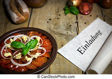Tomato and onion salad on a old wooden table, scroll with word e