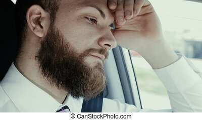 Sad pensive handsome man in car closeup