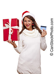 Woman holding a Christmas gift and bank card - Attractive...