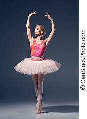 Portrait of the ballerina in ballet pose on a grey...
