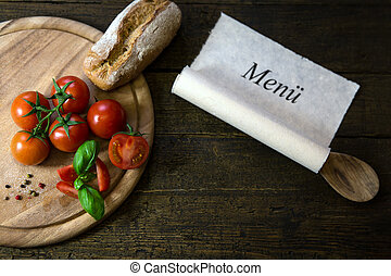 Tomatoes, basil and bread on a wooden table, scroll with word Me