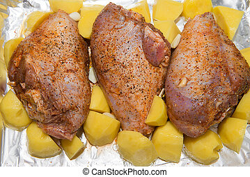 Raw thigh of turkey and potatoes in foil for baking