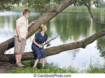 The girl with a rod and the guy looks at it