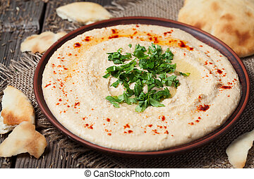 Bowl of hummus, traditional mediterranean smooth salad with...