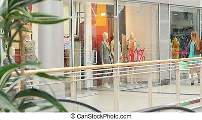 Blonde walks around the glass shop windows. Slow motion
