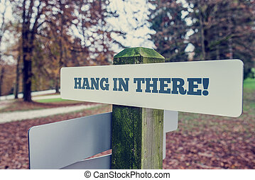 Hang In There motivational message on a rustic signboard on...