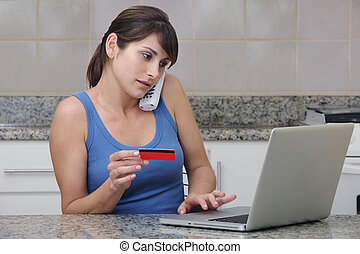 woman with creditcard calling on phone and using the...
