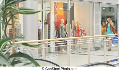 Blonde speaks on a mobile phone and walks around the glass shop windows. Slow motion