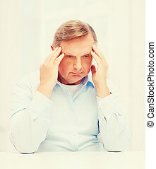 stressed old man holding head at home - oldness, business...