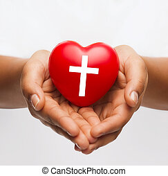 female hands holding heart with cross symbol - religion,...