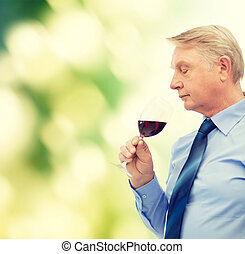 elderly man smelling red wine - alcohol and beverage concept...