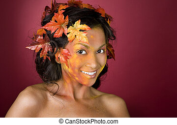 beautiful autumn face - pretty brunette woman wearing leaves...