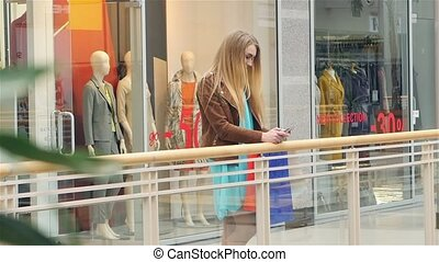 Blonde costs around storefronts and writes message to...