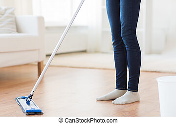close up of woman with mop cleaning floor at home - people,...