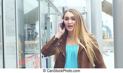 Shopping Beautiful blonde speaks by phone with bags over his...