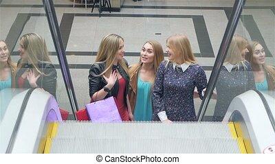 Friends shopping. Two beautiful young women taking escalator in shopping mall Slow motion