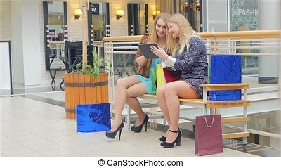 Two young women sitting with shopping bags and used Digital...