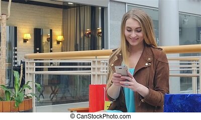 Shopping Woman holding phone on bench the trading floor. Slow motion