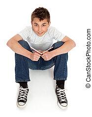 Boy in jeans sitting on floor