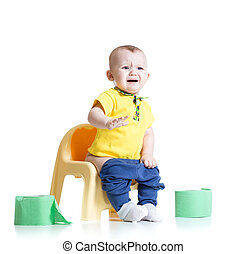 crying child sitting on chamber pot with toilet paper rolls
