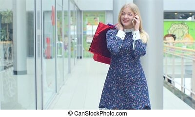 Beautiful blonde goes store and talking on the phone, smiling, looking at shop windows. Slow motion