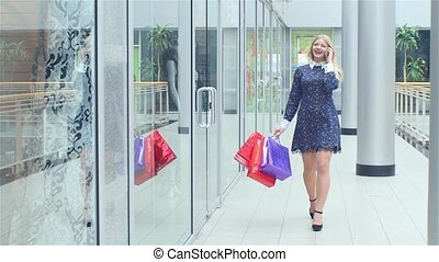 Beautiful blonde goes store and talking on the phone, looking at shop windows. Slow motion