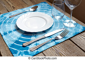 crockery - Empty plate on wooden tabletop with tablecloth...