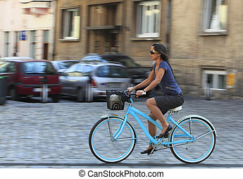 Urban Bicycle Ride - Panning image of a young woman riding...
