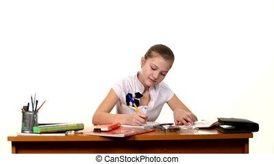 School girl doing her homework and writes essay on white...