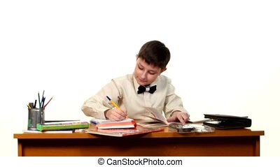 School boy doing his homework thinking about the topic of essay on white background