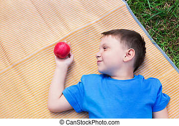 Boy laying on mat and look at apple - Boy laying on mat and...