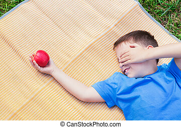 Boy looking at apple and covering eye by hand - Boy laying...