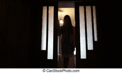 Silhouette of a woman in a doorway front of the window