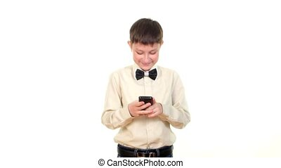 School boy sending message using mobile phone and smiles on...