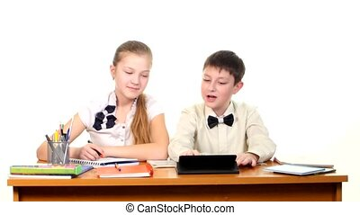 School children sitting by the table, doing homework and discussing something, on white background