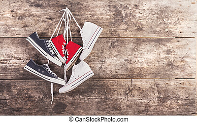 Sports shoes on the floor - Three pairs of sports shoes hang...