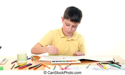 Dark-haired little boy paints colors on white background -...