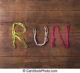 Shoelaces on the floor - Shoelaces run sign on a wooden...